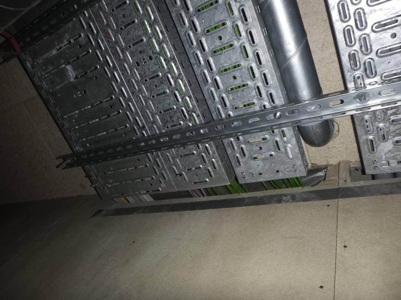 Foto 4. Fout! Aan de zijde van de niet-brandwerende voorzetwand is nauwelijks ruimte aanwezig tussen de kabels en de wand. De kabeldoorvoeren moeten aan beide zijden van de betonnen wand brandwerend worden afgewerkt OP de betonnen wand. Als de niet-brandwerende voorzetwand strak aansluit tegen de doorvoer kan de brandwerende voorziening niet goed zijn werking doen en branddoorslag plaatsvinden.